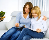 Mother with Teenage Daughter reading fashion Magazine — Stock Photo