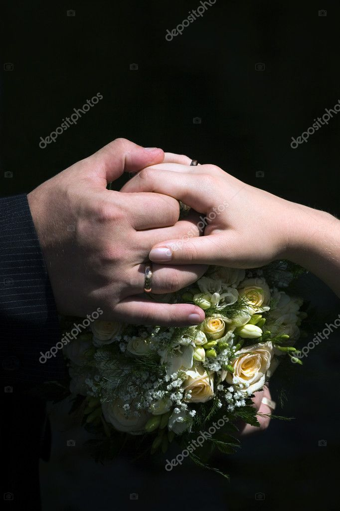 Hands with rings on a wedding bouquet on a black background — Stock Photo #10131061