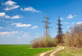 Two power tensions and lines near road — Stock Photo