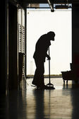 Silhouette of man moping floor — Stok fotoğraf