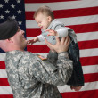 Foto Stock: American Soldier holds his infant son