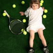 Girl with tennis balls on green background — Stock Photo
