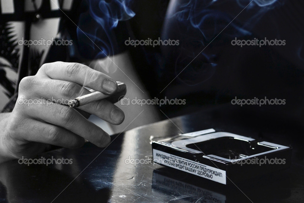 Man hand holding a cigarette with smoke — Stock Photo #9673593