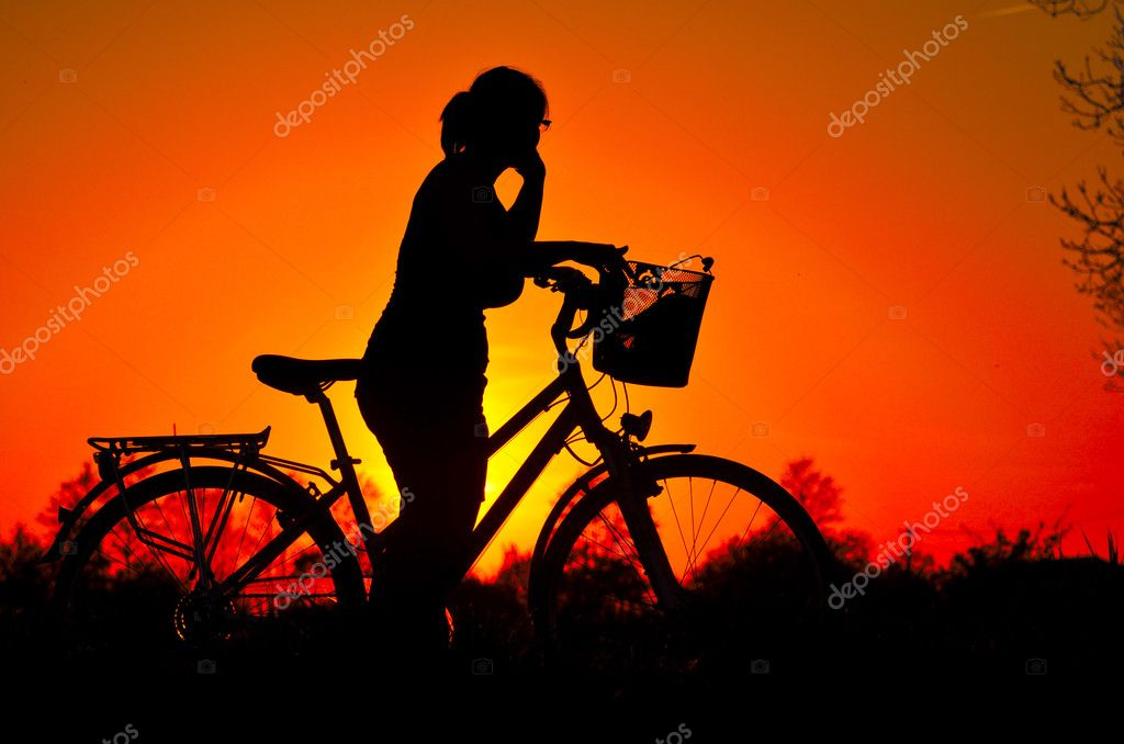 In the picture a young woman riding a bicycle, stopped to admire the splendor of the sunset.  Stock Photo #10448699