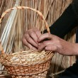 Female hands manually mastering woven wicker basket — Stock Photo