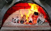Flaming wood in old home brick fireplace — Stock Photo