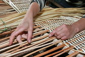 Female hands manually mastering wicker fabric — Stock Photo