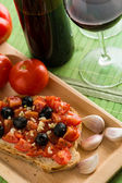 Bruschetta with tomatoes and black olives — Stock Photo