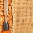 Old steel chisel on Sawdust flakes piled on logs of sack — Stock Photo