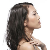 Beautiful Asian woman gently touching her face. — Stock Photo