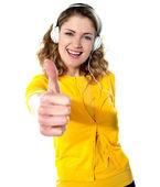 Thumbs-up woman enjoying music — Stock Photo