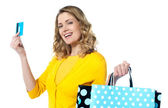 Attractive woman holding cerdit-card with shopping bags — Stock Photo