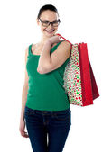 Smiling young female carrying shopping bags — Stock fotografie