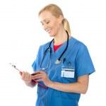 Senior female doctor writing report — Stock Photo