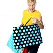 Young girl looking excitedly inside her shopping bag — Stock Photo #10090641