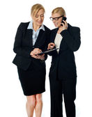 Two females looking at progress report and discussing — Stock Photo