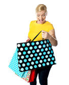 Young girl looking excitedly inside her shopping bag — Stock Photo