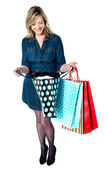 Fashionable woman looking into shopping bags — Stock Photo