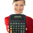 Smiling school girl showing digital calculator — Stock Photo #10223956