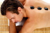 Man relaxing on massage bed with hot stones — Stock Photo