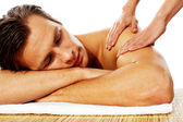 Attractive man having massage in a spa center — Stock Photo