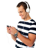 Male teenager with mp3 player and earbuds — Stock Photo