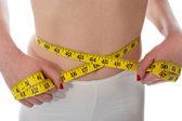 Closeup of tape measure around woman waist — Stock Photo