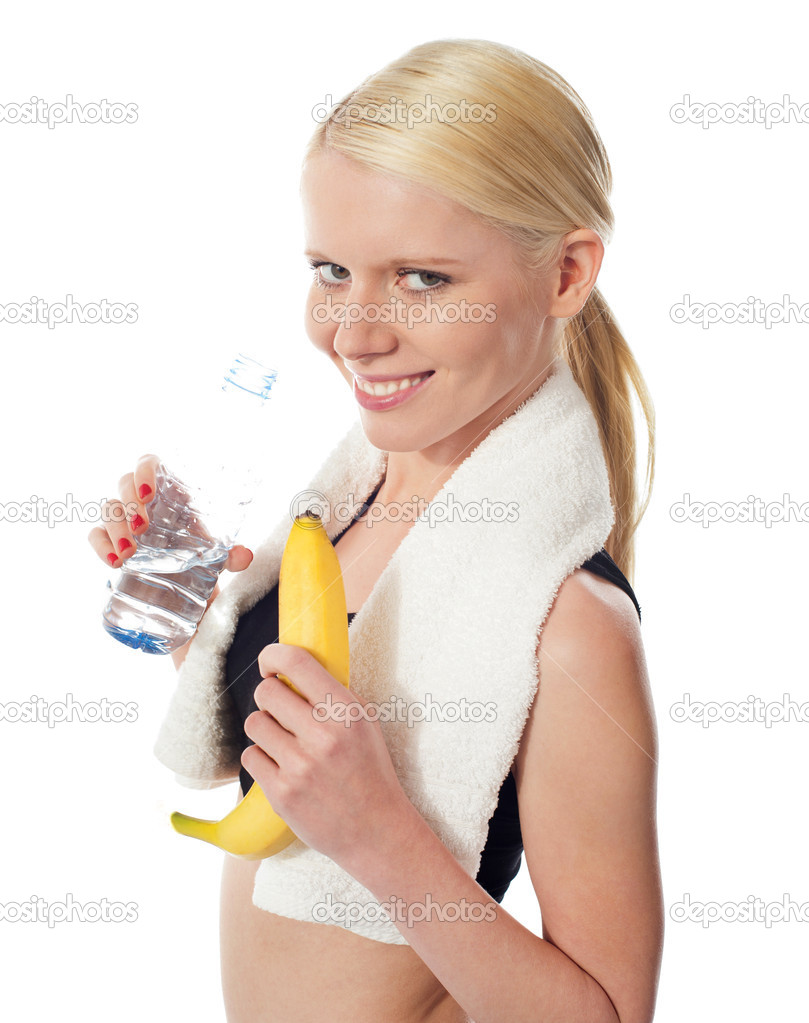 Fitness girl holding water bottle and banana with towel on her neck  Stock Photo #10375474
