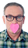 Surprised aged male with paper heart over his mouth — Stock Photo