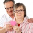 Old couple facing camera with focus on paper heart — Stock Photo