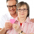 Matured smiling couple holding paper heart - Stock Photo