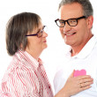 Senior couple with pink heart isolated on white — Stock Photo