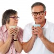 Romantic senior couple holding coffee mugs — Stock Photo