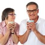 Romantic senior couple holding coffee mugs — Stock Photo