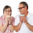 Happy matured couple holding cofee mug - Zdjęcie stockowe