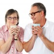 Happy matured couple holding cofee mug - Stock Photo