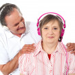 Aged couple enjoying music over white background — Stock Photo