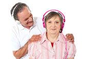 Aged couple enjoying music over white background — Stock Photo
