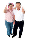 Thumbs-up couple tuned into music — Stock Photo