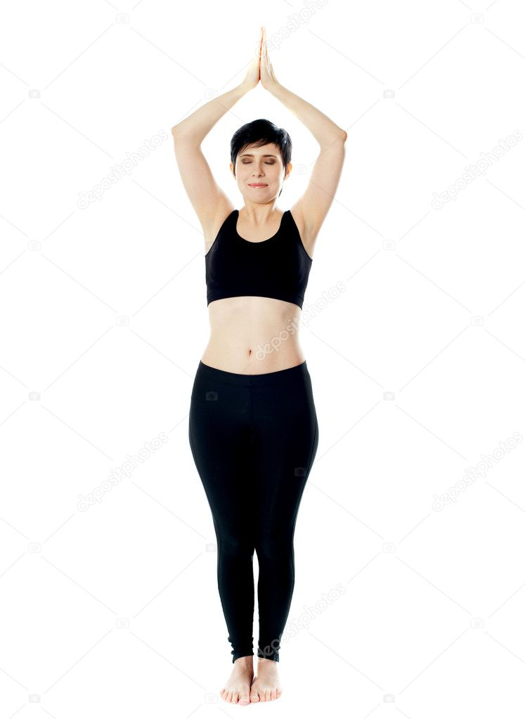 Full-length view of fit woman doing yoga. Standing with hands held together over the head — Stock Photo #10619047