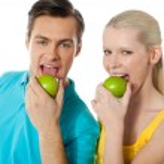 Healthy couple eating fresh green apple — Stock Photo