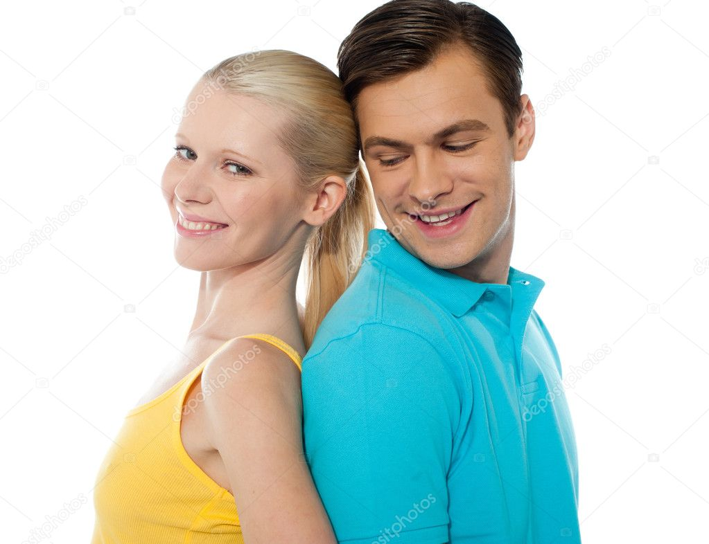 Young couple smiling and posing back to back in front of camera  Stock Photo #9672721