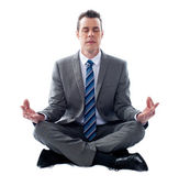 Businessman meditating in lotus position — Stock Photo
