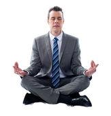 Businessman meditating in lotus position — Stock Photo
