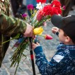 Stock Photo: Little boy gives flowers to veteran