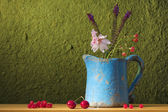 Still life with a can with flowers, cherries and red ber — Stock Photo