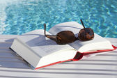 Sunglasses on a book by the swimmingpool — Stock Photo