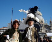 Two in feathers on San Marko Square — Stock Photo