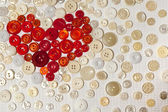 Colorful buttons in shape of heart on white fabric — Stock Photo