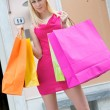 Young blonde shopping woman with bags — Stock Photo